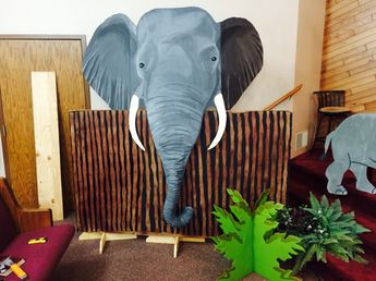 Elephant prop for Aberdeen Alliance Camp Kilimanjaro Safari VBS. My daughter painted the head on cardboard then I attached a dryer vent hose with duck tape for the trunk. We attached him to a fence so we wouldn't have to make the whole body. This guy was huge, about 6 feet from ear to ear and mounted about 7 feet tall. He was a favorite at our church.