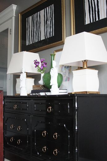 Glossy painted black chest with white tabletop accessories are stunning. Check out the two Bodhisattva statues. The artwork is simple but compliments. The green vase brings one other color into the scheme. Sincerely, JoAnne Craft
