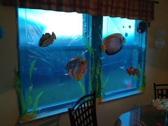 "use blue cellophane to cover windows and add underwater creatures to feel ""under the sea"""