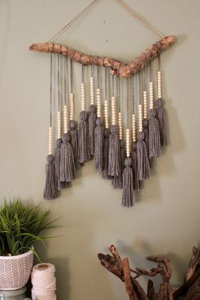 This driftwood hanging can add texture to any empty wall or hang above a headboard in a bedroom. The driftwood foundation was found washed up on the coast of Florida near Fort Lauderdale beach. Yarn was individually measured, cut, and tied to create one singletassel. Small wooden beads were then added on top of each t