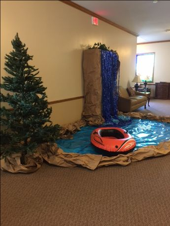 This river/camping scene can work for any spot in your church. This one was used in the foyer area of the church! Display evergreen trees. Create a pond/river using brown craft paper and blue  and cellophane paper. The waterfall was created using a large piece of furniture that is part of the foyer. Great idea to cover what is there! Cover the display case with brown paper. Add blue paper along with foil curtains to give the look and feel of a waterfall! And add a raft!!