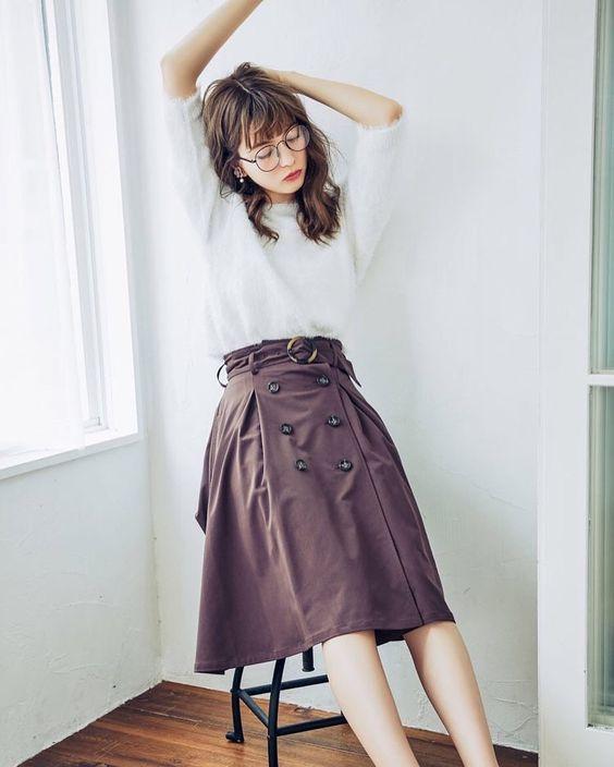 ブラウンのスカートで伸びをする八木アリサ