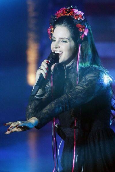 Lana Del Rey performing   black dress and flower crown