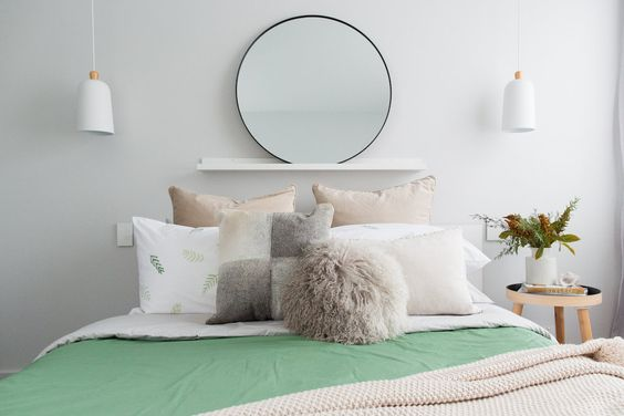 Green and natural bedroom styling with a warm, contemporary twist. Round mirror above bed head, natural fur cushions