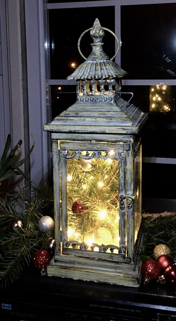 This lantern looks great in almost every season, but especially at Christmas!! Easy: a few cut greens, fairy (rice) light string on battery-operated timer & a few well-placed colored balls!