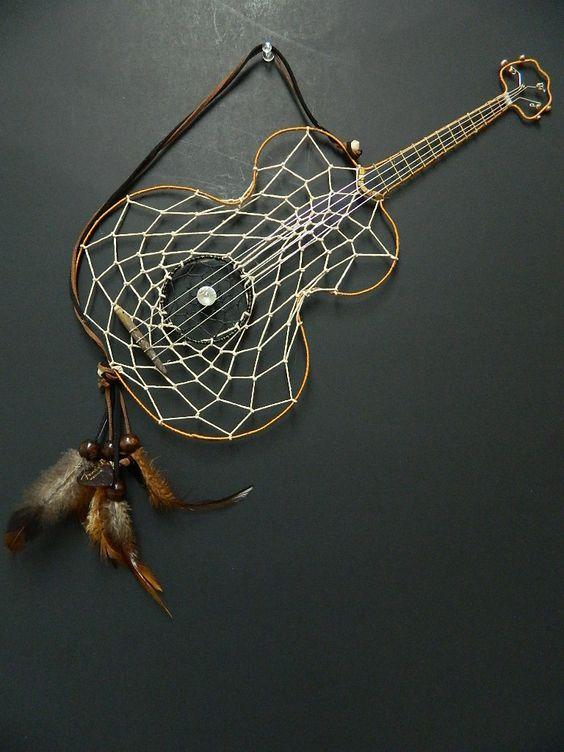 Cantante / cantautore di chitarra acustica Dream Catcher. L'articolo è un design fatto a mano da 16 pollici per 8 pollici con piume naturali marrone, perline in legno marrone e 2 plettri per chitarra. L'anello centrale nero (foro del suono) è intessuto nella fettuccia e accentato con uno strass di cristallo Swarovski.