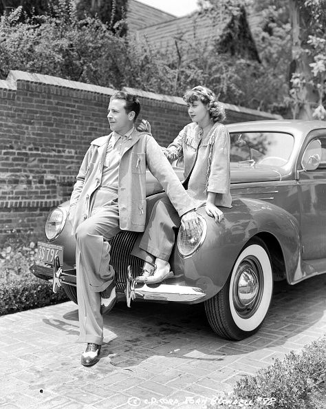 Actors Joan Blondell and Dick Powell sitting together on the hood of a car for Columbia Pictures circa 1936