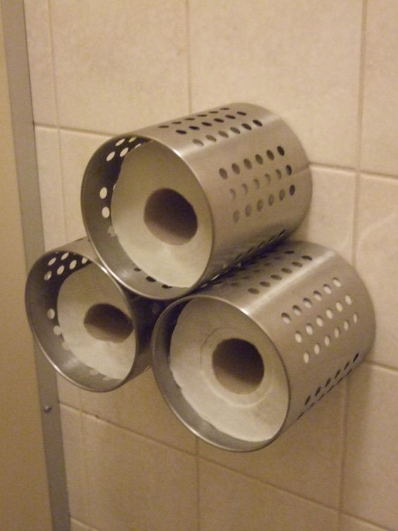 Three IKEA ORDNING utensil holders were attached to the wall in the cafe washroom and are used to store spare toilet rolls.