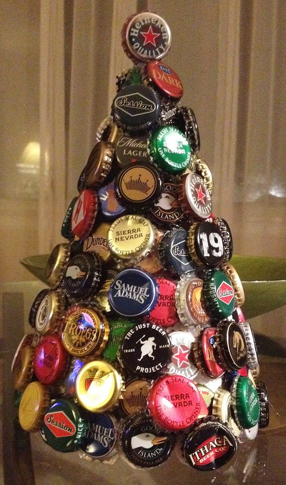 Bottle cap tree I made. You can buy a foam cone to use as the base, but all I used was a piece of poster board rolled up to form the cone form.  I used a hot glue gun to hold the caps on. Just put a small bead of glue along the edge/rim of the cap. The top cap is just 2 caps glued together and pinching the tip of the poster board to stay put.