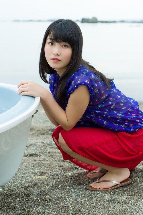 紺色のシャツに赤いスカートの横山由依