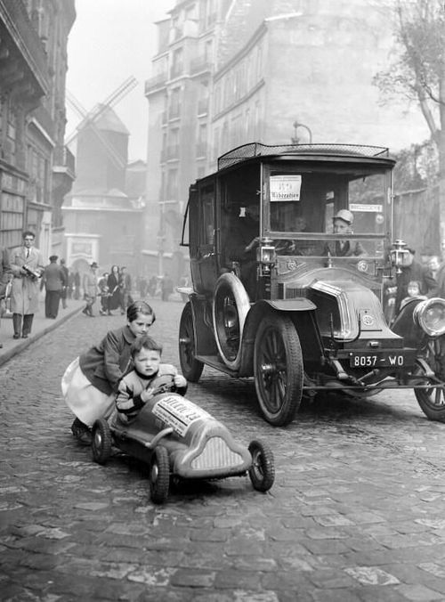 Children playing in Paris, 1920. You can see the Moulin Rouge in the background.  #vintagephotos #1920s  #paris