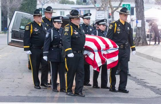 """Newman police officers carry the body of their slain colleague Cpl. Ronil """"Ron"""" Singh during his funeral."""