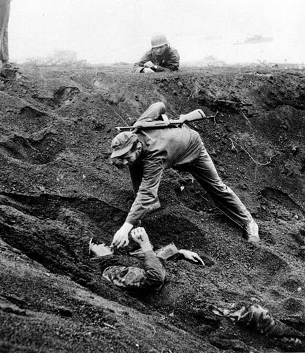 Marine gives cigarette to Japanese soldier on Iwo Jima